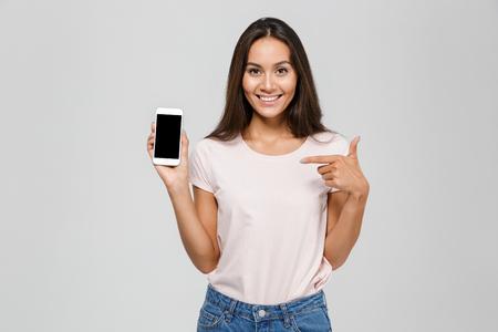 うれしそうな画面の携帯電話でアジアの女性 poinitng 指を笑顔と白い背景に分離カメラ目線の肖像画