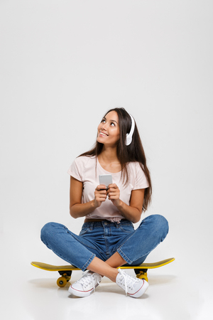 Portrait of young cheerful girl in white headphone chatting by phone, sitting on skateboard, looking up, isolated over white background