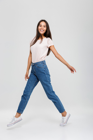 Full length portrait of a casual young asian woman jumping and looking at camera isolated over white background