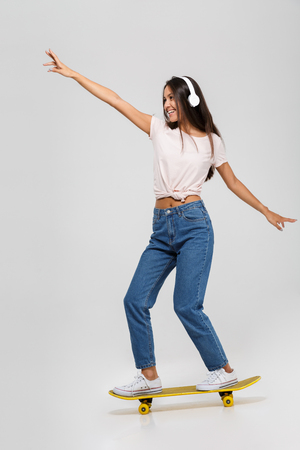 Full length portrait of a happy funny asian woman in headphones listening to music while riding on a skateboard isolated over white background