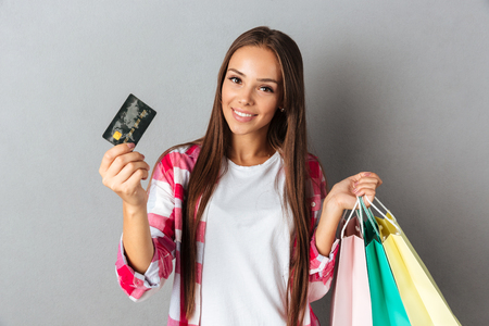 Young girl holding shopping bags and credit card, looking at camera, isolated on gray background