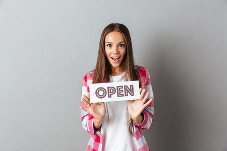 オープン サインは、灰色の背景の上に保持している驚きの若いブルネットの女性の肖像画 写真素材