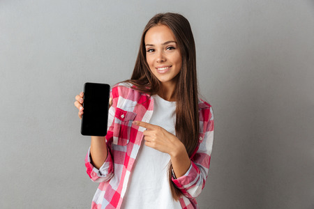 Smiling casual girl pointing finger at blank screen mobile phone while standing isolated over gray background Фото со стока