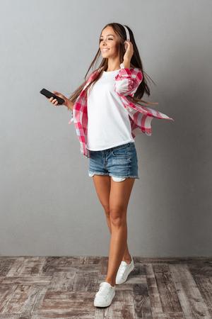 Full-length portrait of smiling brunette girl with long hair, listening music with white headphones, over gray wall Stock Photo