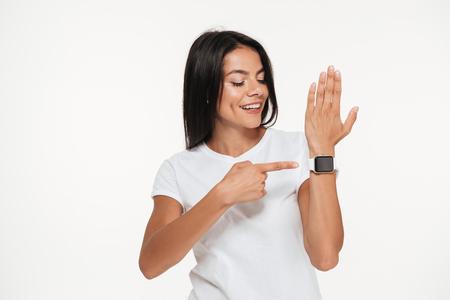 彼女の手首は、白い背景で隔離のスマートな腕時計で指を指して幸せな若い女の肖像
