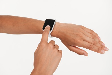 Close up portrait of female hands using wrist smart watch isolated over white background Stock Photo