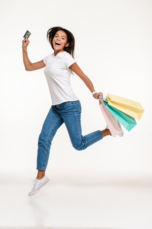Full length portrait of a happy casual woman jumping while holding credit card and colorful shopping bags isolated over white background 版權商用圖片
