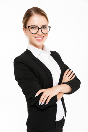Vertical image of smiling blonde business woman in eyeglasses posing sideways with crossed arms and looking at the camera over white background
