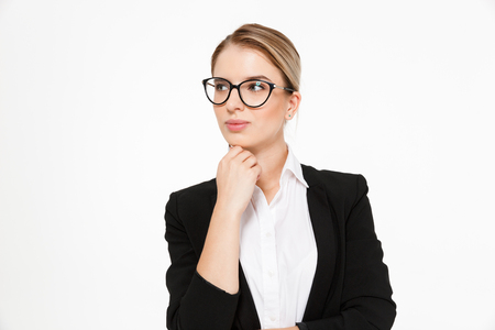 Attractive blonde business woman in eyeglasses holding hand near chin and looking away over white background Stok Fotoğraf - 88451339