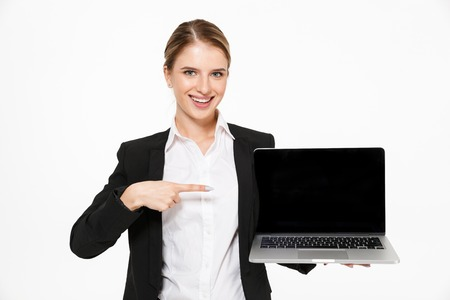 Happy blonde business woman showing blank laptop computer screen and pointing at him while looking at the camera over white background