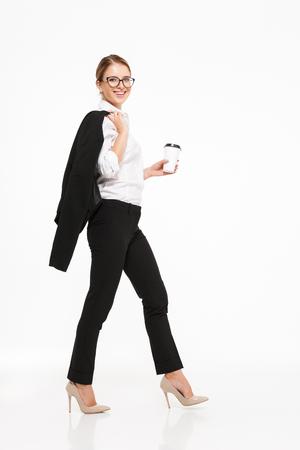 Het volledige beeld van het lengte zijaanzicht van glimlachende blonde bedrijfsvrouw in oogglazen die in studio met kop van koffie lopen en de camera over witte achtergrond bekijken