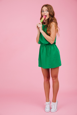 Full length portrait of a pretty smiling woman in dress licking ice cream while standing and looking away at copy space isolated over pink background