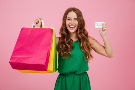 Portrait of a cheerful pretty woman showing shopping bags and a credit card isolated over pink background