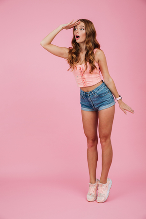 Full length portrait of a beautiful slim woman in summer clothes looking far away with hand at her forehead isolated over pink background