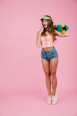 Full length portrait of a shocked astonished woman in summer clothes posing and holding hand at her face while standing with a skateboard isolated over pink background
