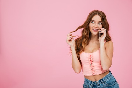 Portrait of a playful beautiful woman in summer clothes talking on mobile phone while standing and looking away at copy space isolated over pink background