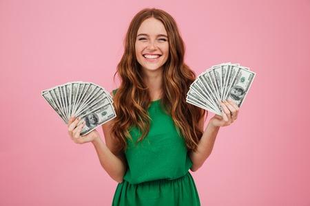 각 손에 돈 지폐의 무리를 들고 핑크 배경 위에 절연 카메라를보고 긴 머리를 가진 웃는 젊은 여자의 초상화