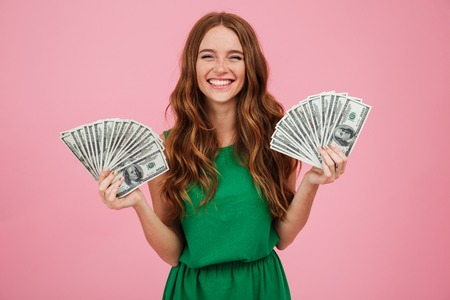 Portrait of a smiling young woman with long hair holding bunch of money banknotes in each hand and looking at camera isolated over pink background