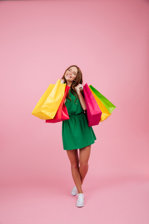 Full length portrait of a happy satisfied woman in dress standing and holding colorful shopping bags isolated over pink background Фото со стока