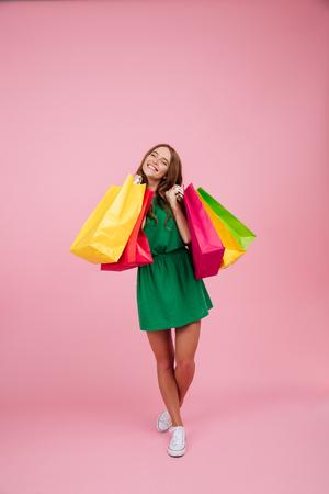 Volledig lengteportret van een gelukkige tevreden vrouw in kleding die en kleurrijke die het winkelen zakken bevinden zich houden over roze achtergrond worden geïsoleerd