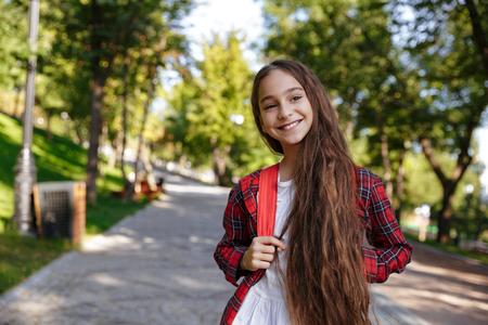 souriante jeune fille brune posant dans le parc et en détournant les yeux