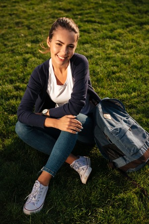 Portrait of a happy cheerful student girl with backpack sitting on the lawn at park and looking at camera