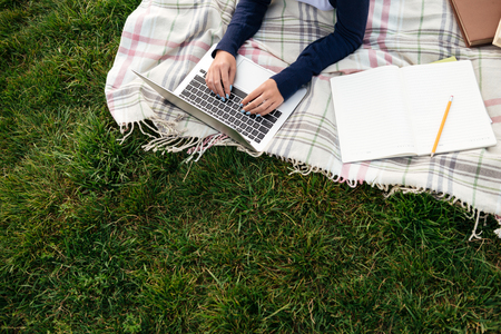 Top view of a female student studying on laptop computer while lying on the grass with a textbook Banco de Imagens