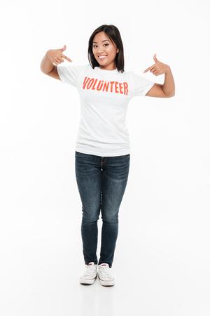 立っていると、白い背景で隔離のカメラを見ながら 2 本の指を指しているボランティア t シャツの幸せな若いアジア女性の完全な長さの肖像画