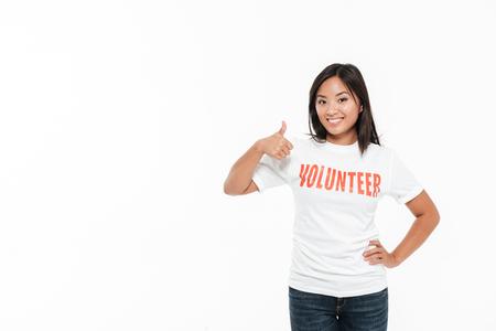 立っていると白い背景上分離された大きなコピー スペースを持つジェスチャー親指を示すボランティア t シャツの幸せ満足しているアジアの女性の 写真素材