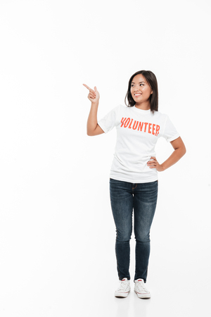 Full length portrait of a pretty joyful asian woman in volunteer t-shirt standing and pointing finger away at copy space isolated over white background