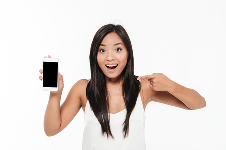 Portrait of an excited happy casual asian woman holding and pointing finger at blank screen mobile phone isolated over white background