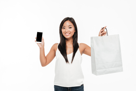 Portrait of a happy smiling asian woman showing blank screen mobile phone and a shopping bag isolated over white background