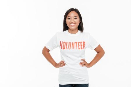 altruismo: Retrato de una mujer asiática joven alegre en la camiseta voluntaria que se coloca con las manos en caderas y que mira la cámara aislada sobre el fondo blanco Foto de archivo