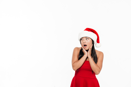 Portrait of a surprised young asian woman in red christmas costume looking away at copy space isolated over white background