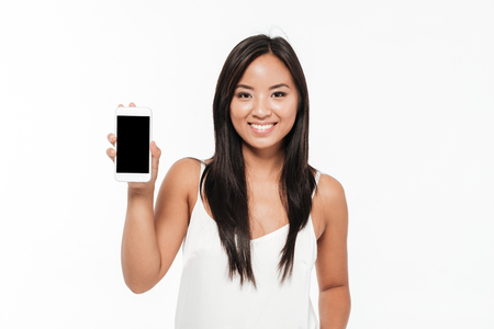 Portrait of a cheerful casual asian woman showing blank screen mobile phone isolated over white background Фото со стока