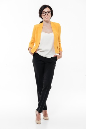 Full length portrait of a smiling pretty woman in eyeglasses and a jacket posing while standing and looking at camera isolated over white background Stock Photo