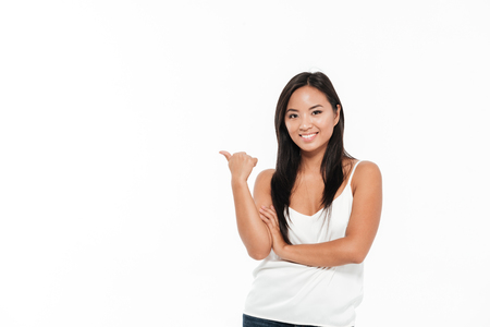 Portrait of a smiling attractive asian woman pointing finger away at copy space and looking at camera isolated over white background