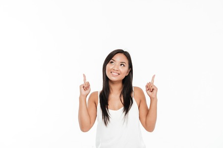 Portrait of a happy smiling asian woman pointing two fingers up at copy space isolated over white background