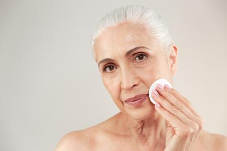 흰색 배경 위에 격리 목화 패드와 메이크업을 제거하는 사랑스러운 절반 벌 거 벗은 할머니의 아름다움 초상화