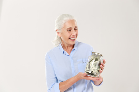 Happy senior lady with closed eyes holding glass bank with dollars, isolated on white background Stock Photo