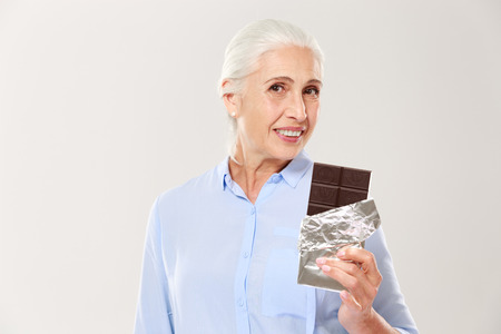 Portrait of charming old lady holding chocolate bar, looking at camera, isolated on white background
