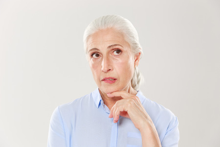 Close-up of thinking beautiful old woman in blue shirt, looking up, isolated over white background