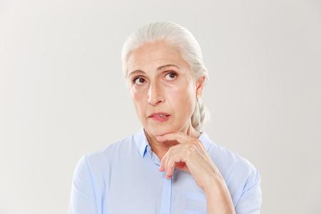 Nahaufnahme des Denkens der schönen alten Frau im blauen Hemd, oben schauend, lokalisiert über weißem Hintergrund