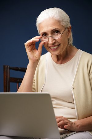 Image of amazing cheerful old woman sitting over dark blue background using laptop computer. Looking camera.