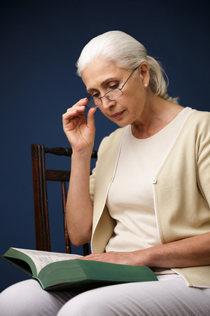 Picture of serious old woman sitting over dark blue background reading book. Looking aside.
