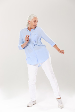 Full-length photo of beautiful old lady, dancing and singing over white background