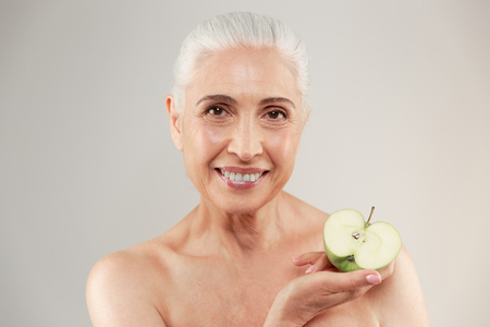 half naked: Beauty portrait of a smiling half naked elderly woman holding sliced green apple and looking at camera isolated over white background