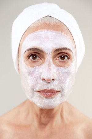 Close up beauty portrait of a mature woman with towel wrapped around her head in facial cream mask isolated over white background Foto de archivo