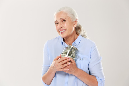 Happy smiling mature woman hugging her glass jar with dollars, isolated over white background