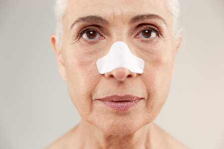 Close up beauty portrait of an old half naked lady with clear-up patches on her nose to remove blackhead looking at camera isolated over white background Stock Photo